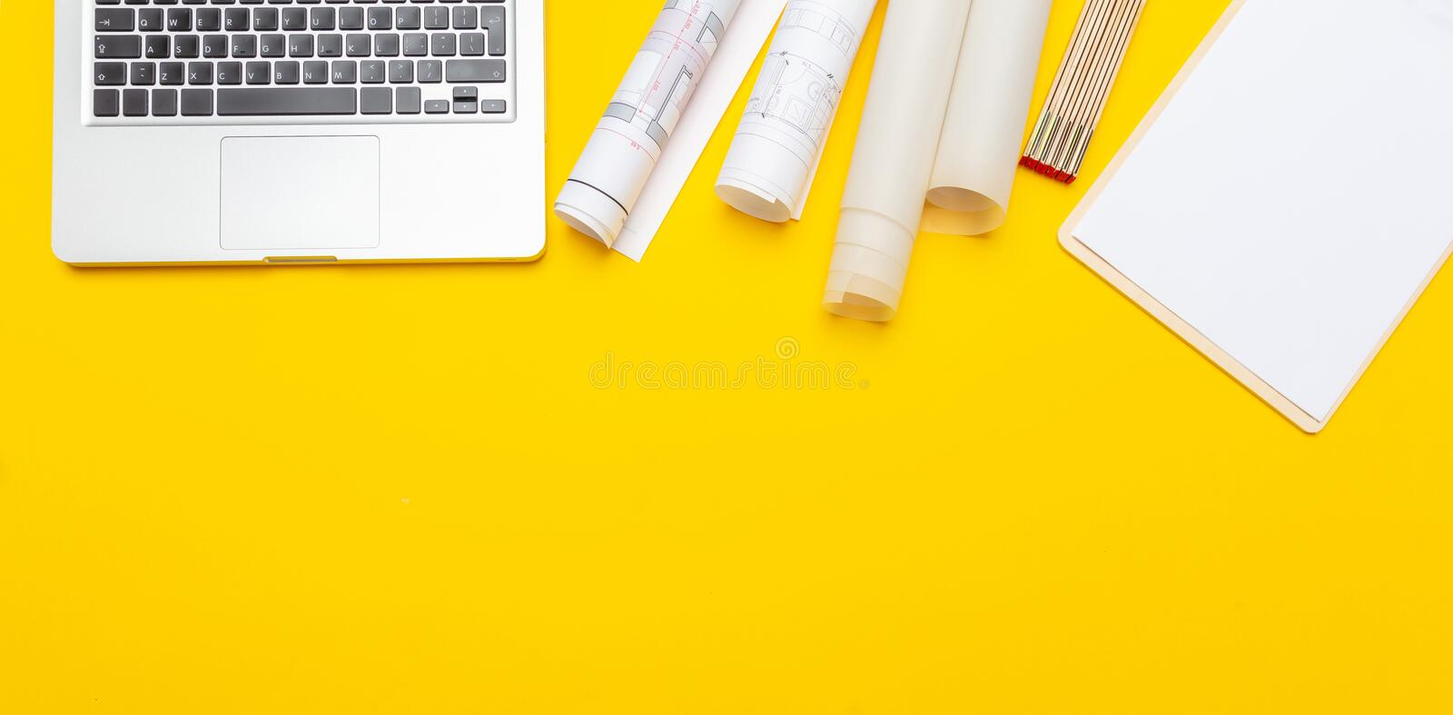 Project blueprints, notepad and computer laptop on yellow color stock images