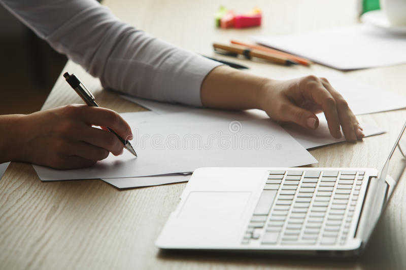 Project concept. Female hands doing paperwork and using laptop. Project concept royalty free stock image
