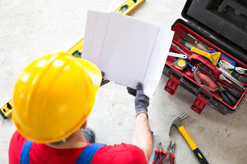 Project documentation and apartment schematics. In the hands of an ambitious worker royalty free stock photos