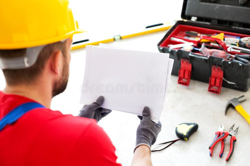 Project documentation and apartment schematics. In the hands of an ambitious worker royalty free stock photography