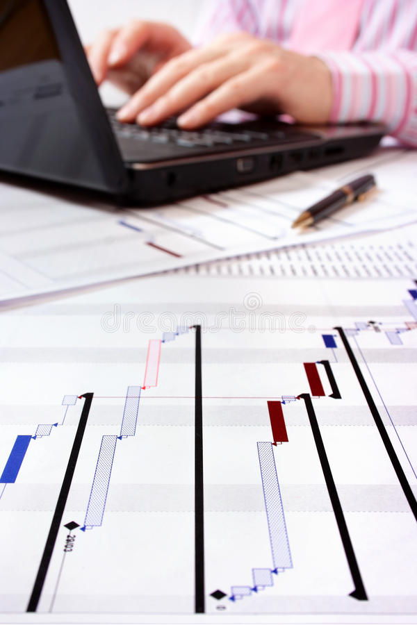 Project Gantt chart with laptop in background. Gantt chat with project manager working on laptop in background. Selective focus on foreground stock images