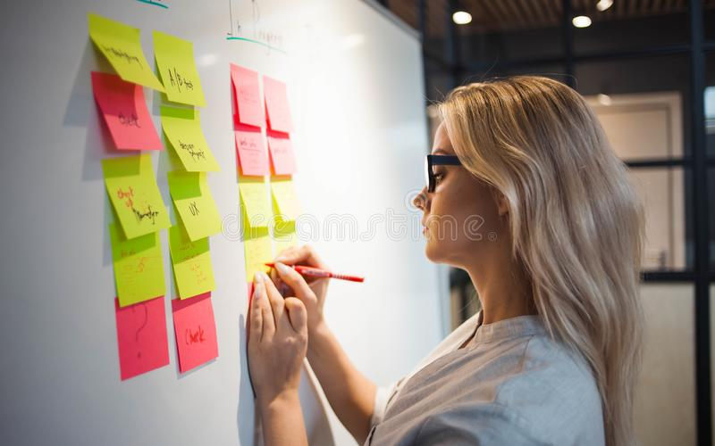 Project management, agile methodology. young business woman in the office. Are planning product development and support. Project manager glue sticky stickers on stock photo