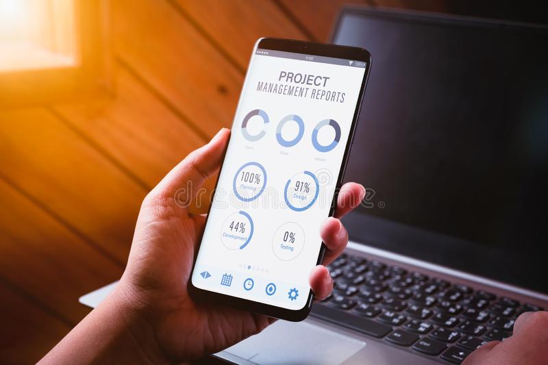 Project management dashboard reports data analytics concept. Close up of young business woman holding smart phone with project stock photography