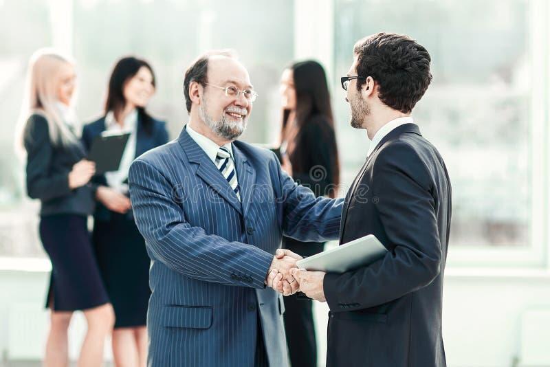 Project manager che stringe le mani con l'impiegato prima del seminario fotografia stock libera da diritti