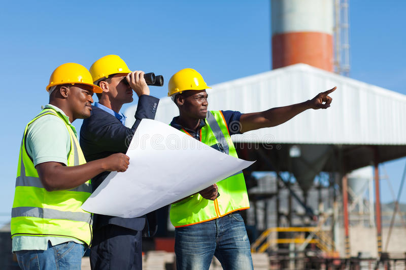 Project manager construction. Project manager visiting construction site with construction workers stock photo