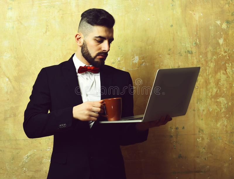 Project manager with serious face puts coffee on laptop stock images