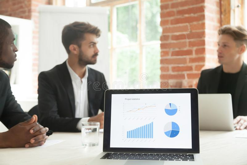 Project statistics on laptop screen with businessmen talking at stock photo
