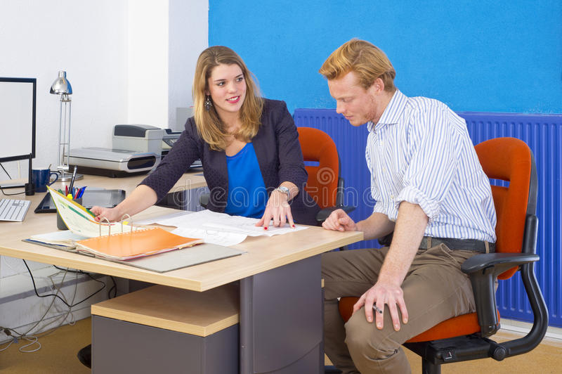 Project team meeting. Two coworkers, forming a project team, discussing a design brief and some technical drawings, spred out over a desk in an office stock photos