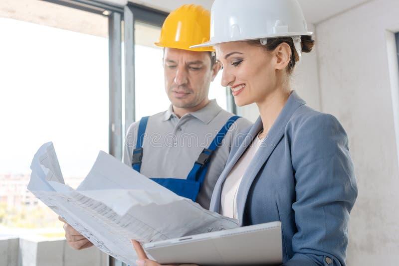 Projecteigenaar en bouwvakker tijdens goedkeuring stock foto