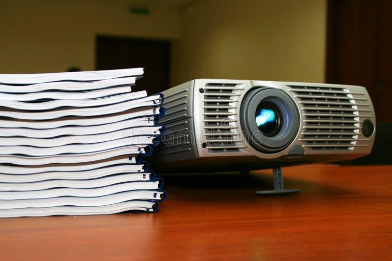 Projecteur avec la pile des livres image libre de droits