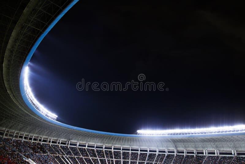 Projecteurs et projecteurs à un stade la nuit image stock