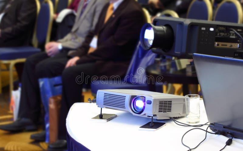 Projecteurs sur le fond des gens s'asseyants de tache floue photos stock