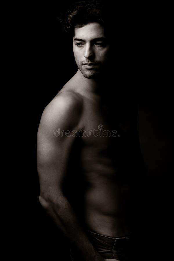 Projectile sexy de jeune homme dans le backround noir photo libre de droits