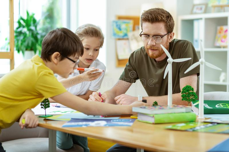 Concentrated bearded teacher spending time with his curious pupils. Projective poster. Concentrated bearded teacher spending time with his curious pupils in stock image