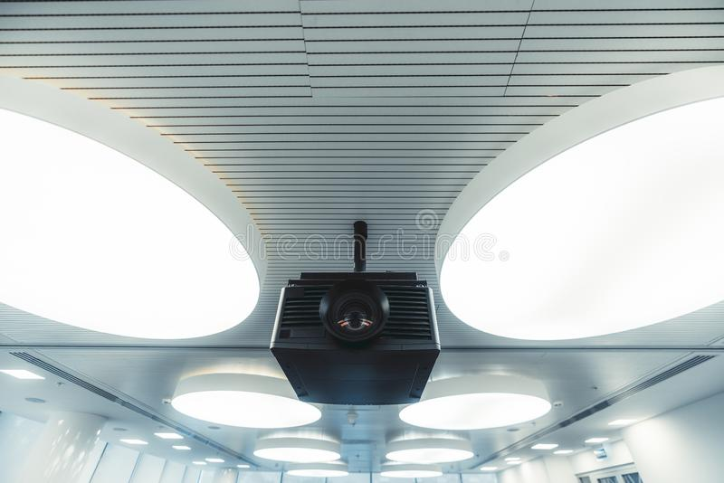 A projector in a bright meeting room. Wide-angle view of a black modern projector with a plastic case and a huge lens with aberrations on it, mounted to the royalty free stock images