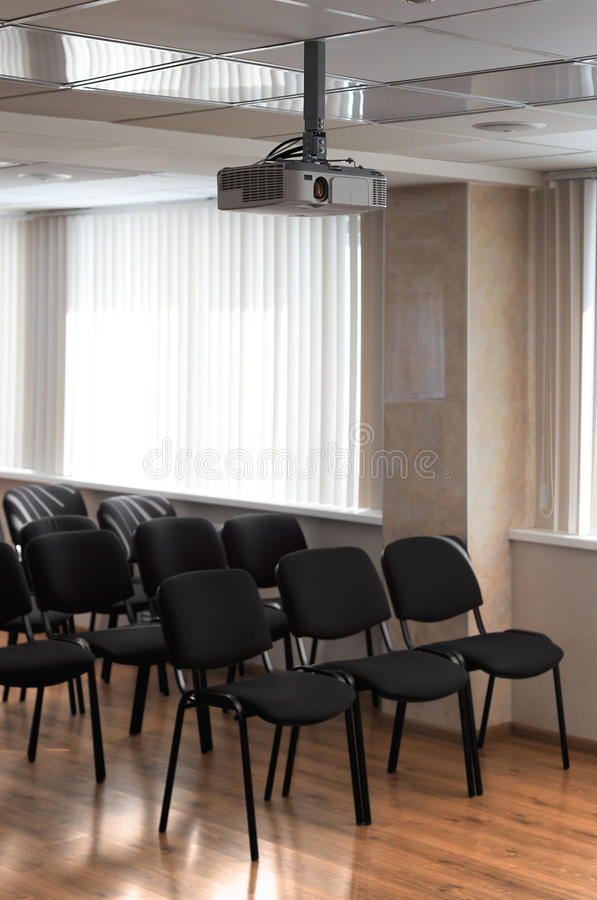 Projector hang on ceiling of empty sunlit meeting room. With black chairs standing in rows stock photos