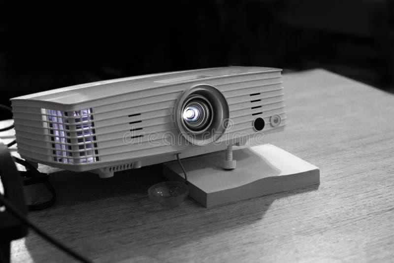 Projector op de lijst moderne laptop die op witte achtergrond wordt geïsoleerdd stock afbeelding