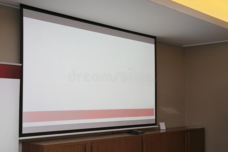 Projector Screen. At Wall in Dark Conference Hall stock images