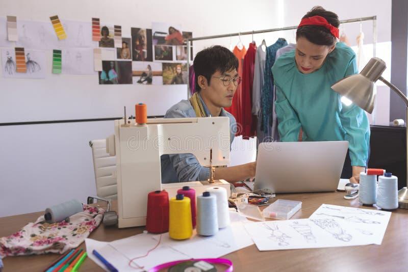 Projektanci modzi dyskutuje nad laptopem przy biurkiem w projekta studiu zdjęcia stock