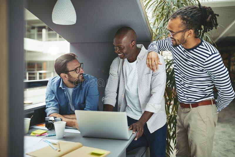 Projektanci pracujący nad laptopem w kapsule na zebranie biurowe zdjęcie royalty free