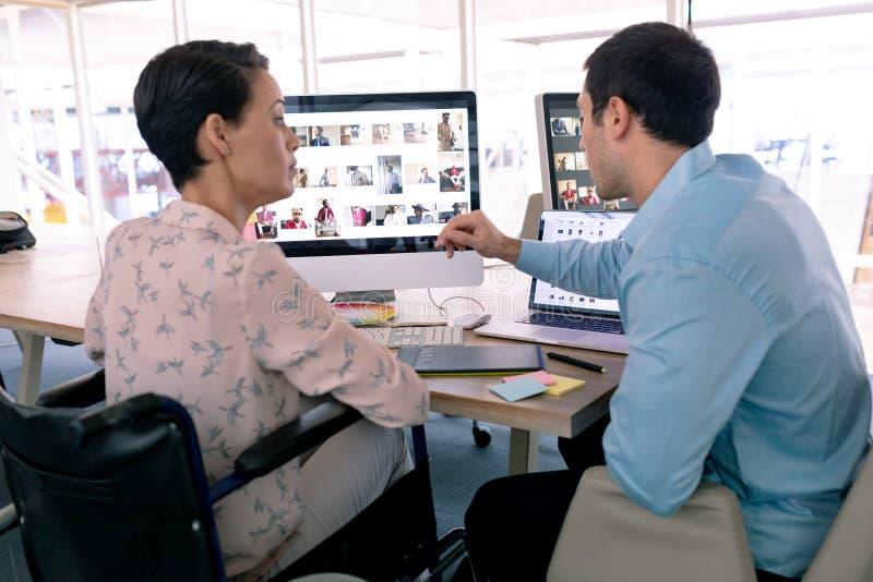 Projektant grafik komputerowych dyskutuje nad komputerem przy biurkiem w nowożytnym biurze zdjęcie stock