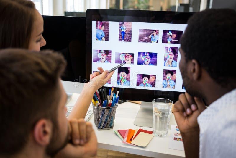 Projektant grafik komputerowych dyskutuje nad komputerem przy ich biurkiem obrazy stock