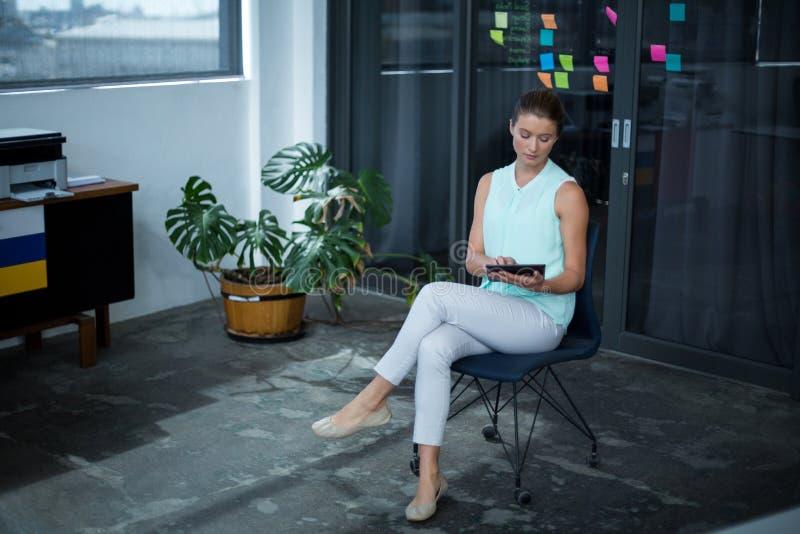 Projektant grafik komputerowych obsiadanie na krześle i używać cyfrową pastylkę obraz stock