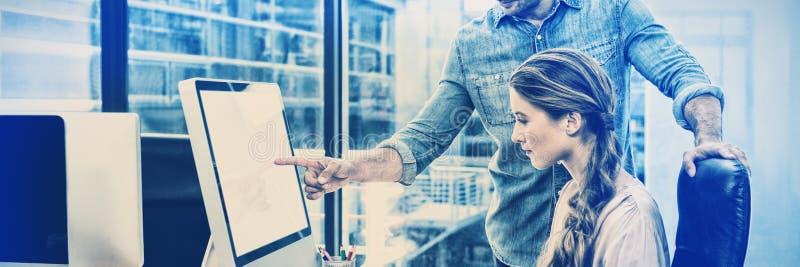 Projektant grafik komputerowych pracuje przy biurkiem z kolegą zdjęcia stock