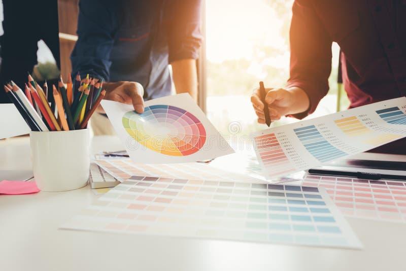 Projektant grafik komputerowych pracuje przy jego biurkiem i wybiera koloru toge zdjęcie royalty free