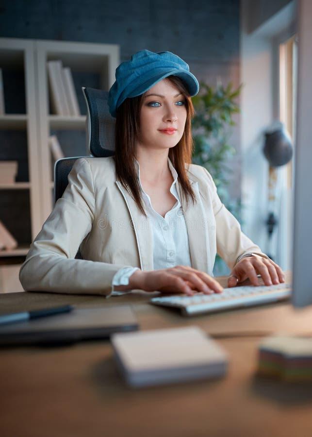 Projektant grafik komputerowych przy pracą - kobieta pracuje póżno na komputerze przy fotografia stock