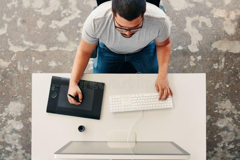 Projektant grafik komputerowych używa cyfrową grafiki pastylkę, desktop i zdjęcia stock