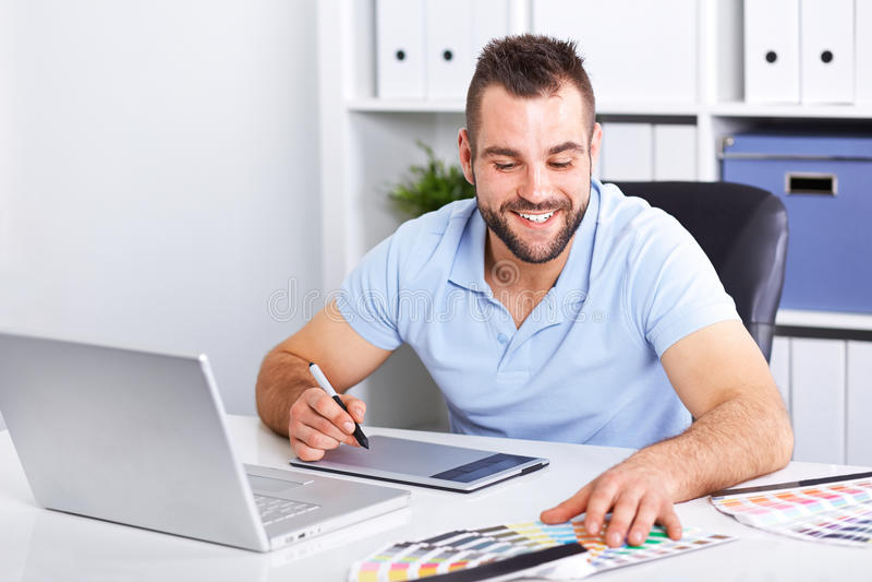 Projektant grafik komputerowych używa grafiki pastylkę w nowożytnym biurze zdjęcia royalty free