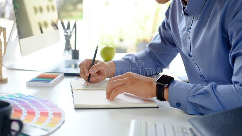 Projektant grafiki współpracujący z papierem do notebooków i komputerem na biurku obrazy royalty free