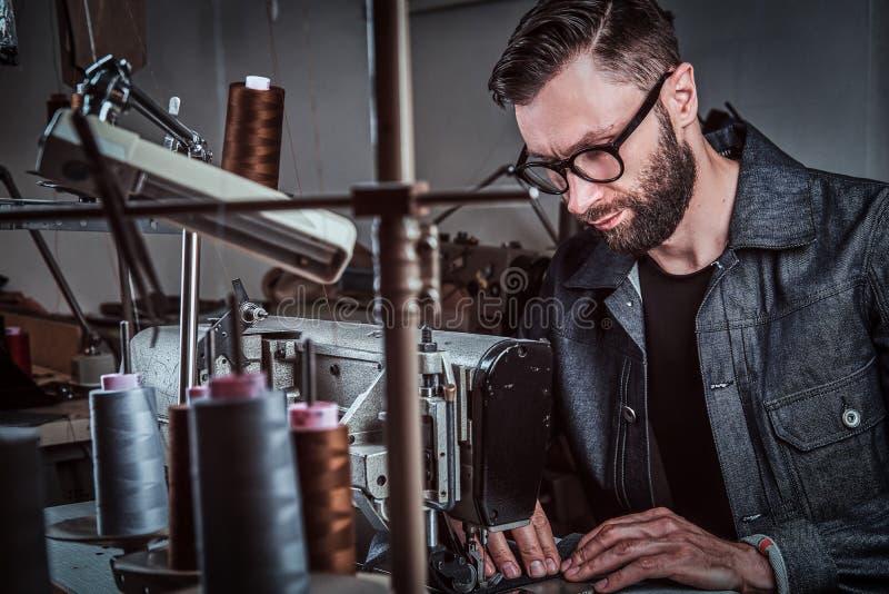 Projektant mody jest szwalny odziewa szwalną maszyną przy warsztatem zdjęcie royalty free