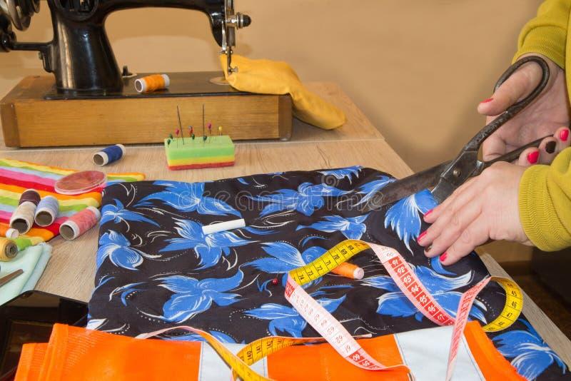 Projektant mody tnąca tkanina obok szwalnej maszyny obraz royalty free