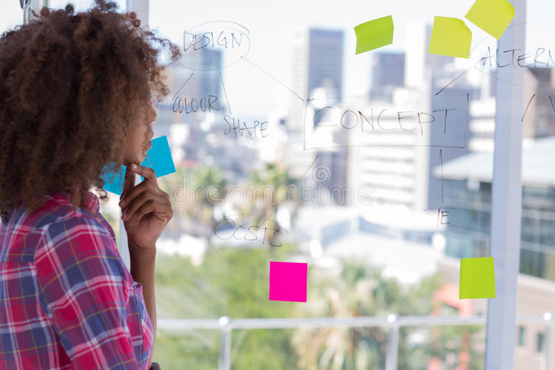 Projektant patrzeje flowchart na okno zdjęcia stock
