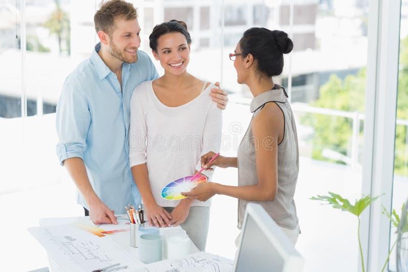 Projektant wnętrz pokazuje colour koło szczęśliwi młodzi klienci zdjęcie royalty free