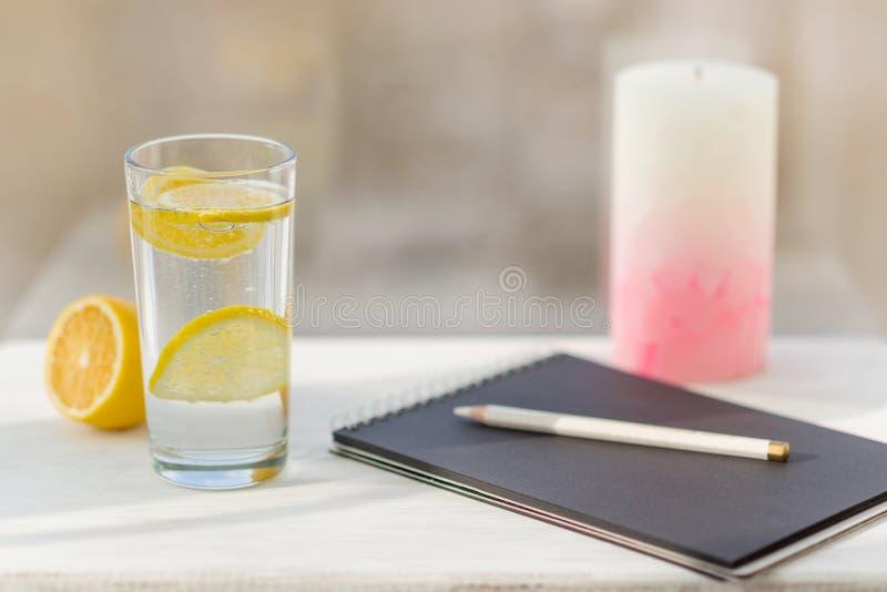 Projektanta czarny notatnik, ołówek, szkło woda mineralna z cytryną obraz royalty free