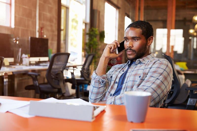 Projektanta obsiadanie Przy spotkanie stołem Opowiada Na telefonie komórkowym fotografia stock