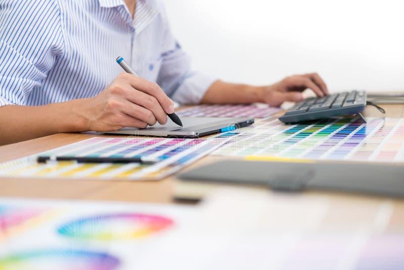 Projektanta redaktor przy praca rysunkiem kreśli nowego projekt na graficznej pastylki i kolor palety obsiadaniu przy biurkiem z  obraz royalty free