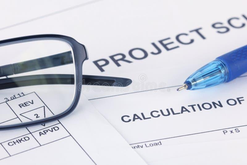 Projektberäkningsdokument med pennan och glasögon arkivfoton