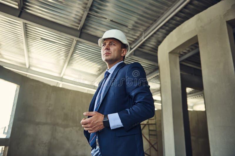Projektchefen i dräkt står på arbetsplats royaltyfria foton