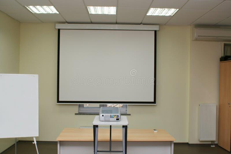 Projektionsbildschirm im Sitzungssaal mit Projektor auf Tabelle lizenzfreies stockfoto