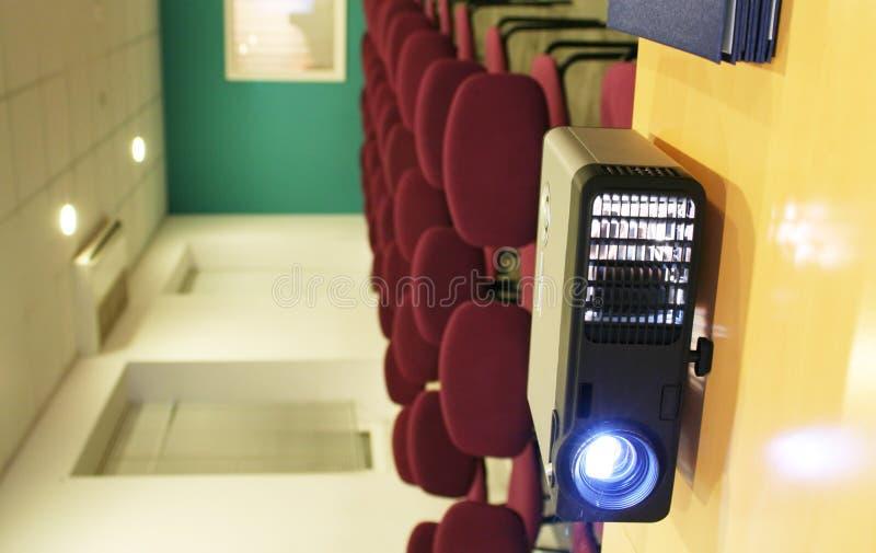 Projektor auf Tabelle mit Stühlen hinter (Vertikale) stockbild