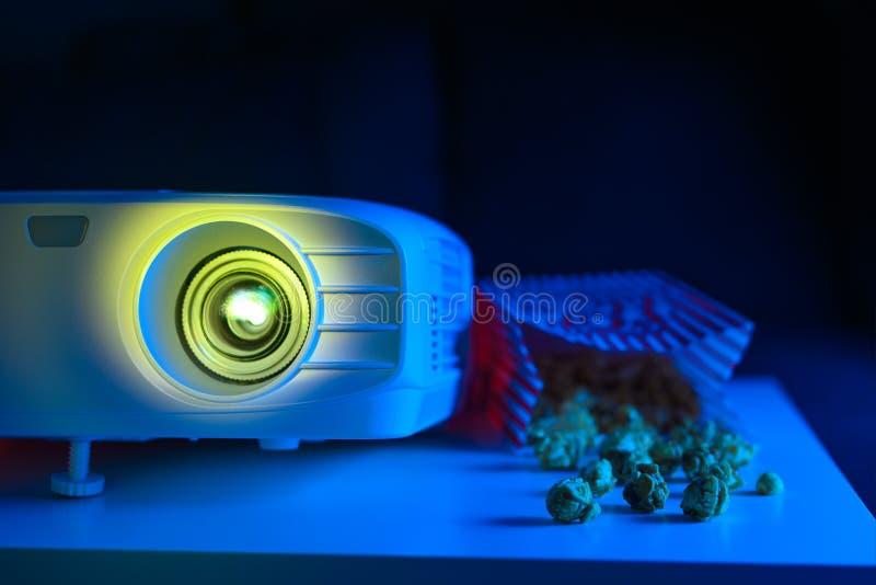 Projektor für Filme zu Hause oder ein Kino mit Popcorn auf dunklem Hintergrund lizenzfreie stockfotografie