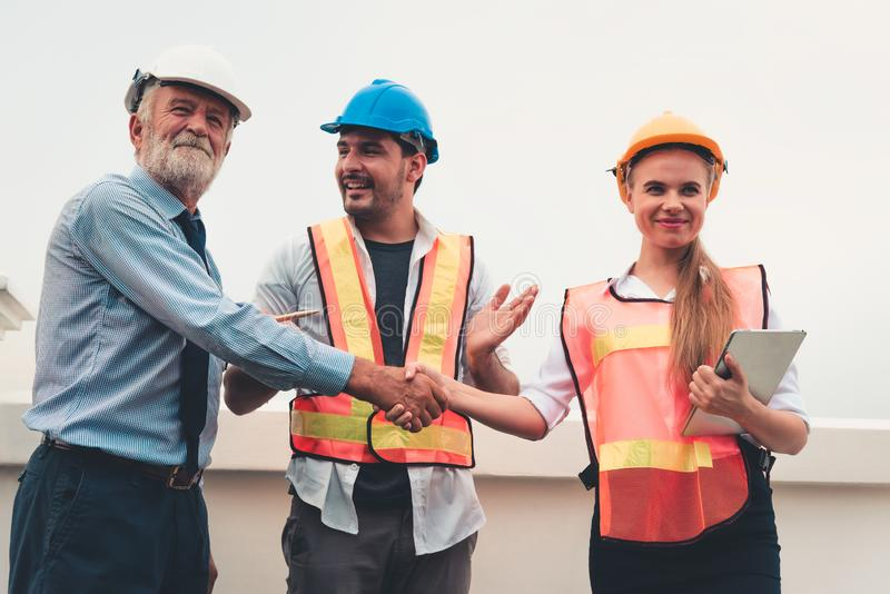 Projektstyrgruppen av teknikerer och arkitekten är handskakningen arkivfoton