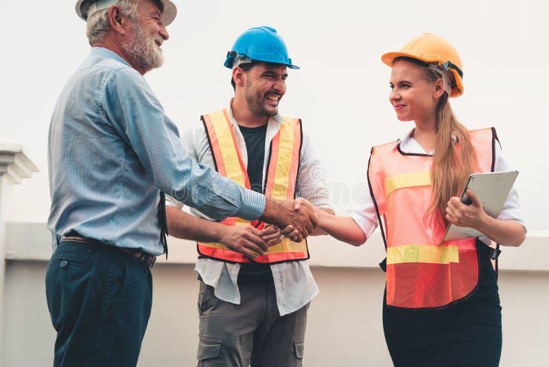 Projektstyrgruppen av teknikerer och arkitekter är handshak royaltyfri bild