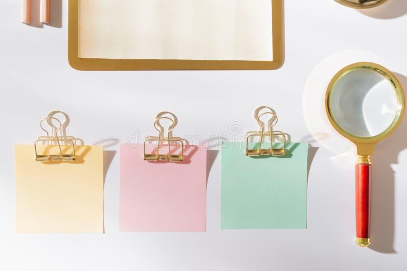 Projektująca pracująca przestrzeń z złocistymi biurowymi dostawami i kolor kleistą notatką obrazy stock