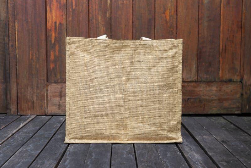 Projektuje brown jutową sklep spożywczy torbę na drewnianej podłoga obrazy stock