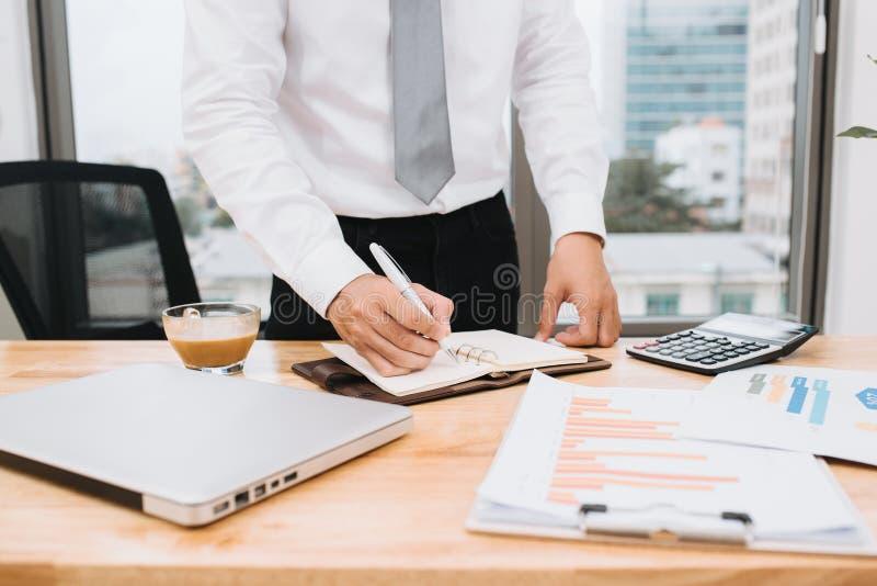 Projet de travail de planification occasionnel d'homme d'affaires, ?crivant la note avec l'ordinateur portable et le caf? sur la  photographie stock